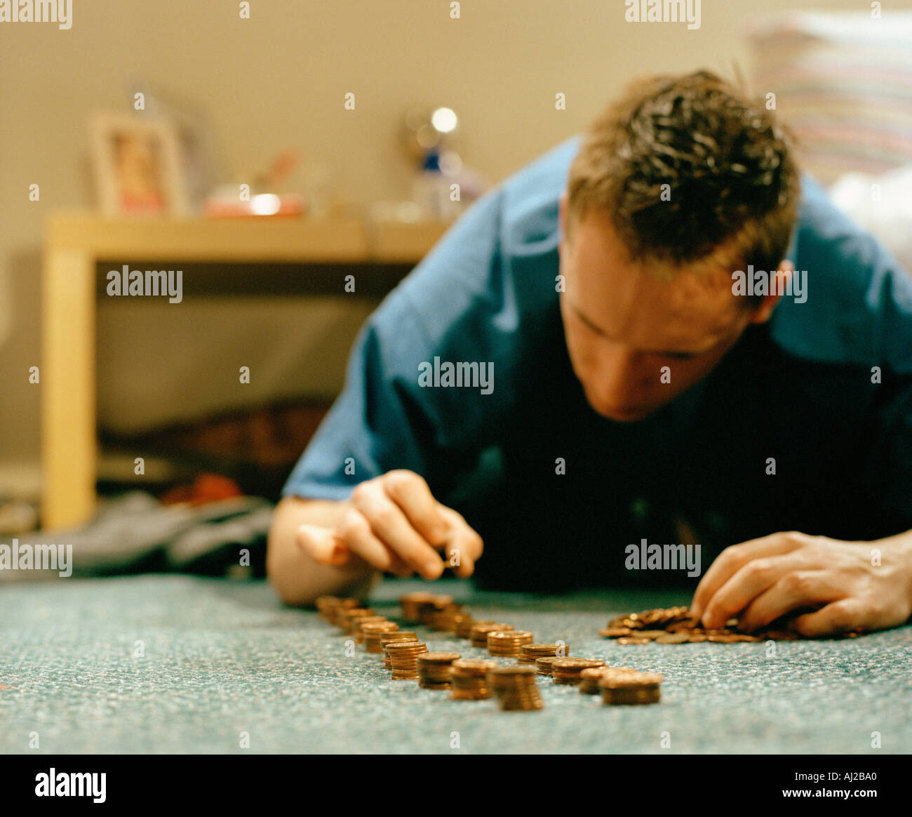 young male lining up coins on floor - Stock Image