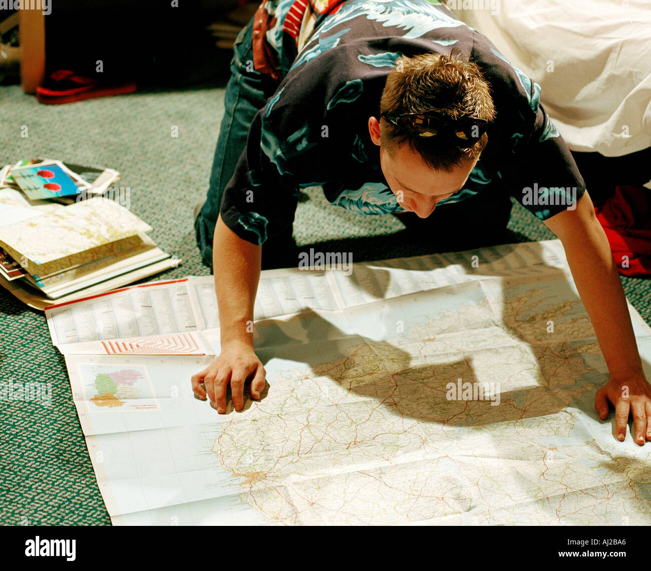 young male in bedroom leaning over map - Stock Image
