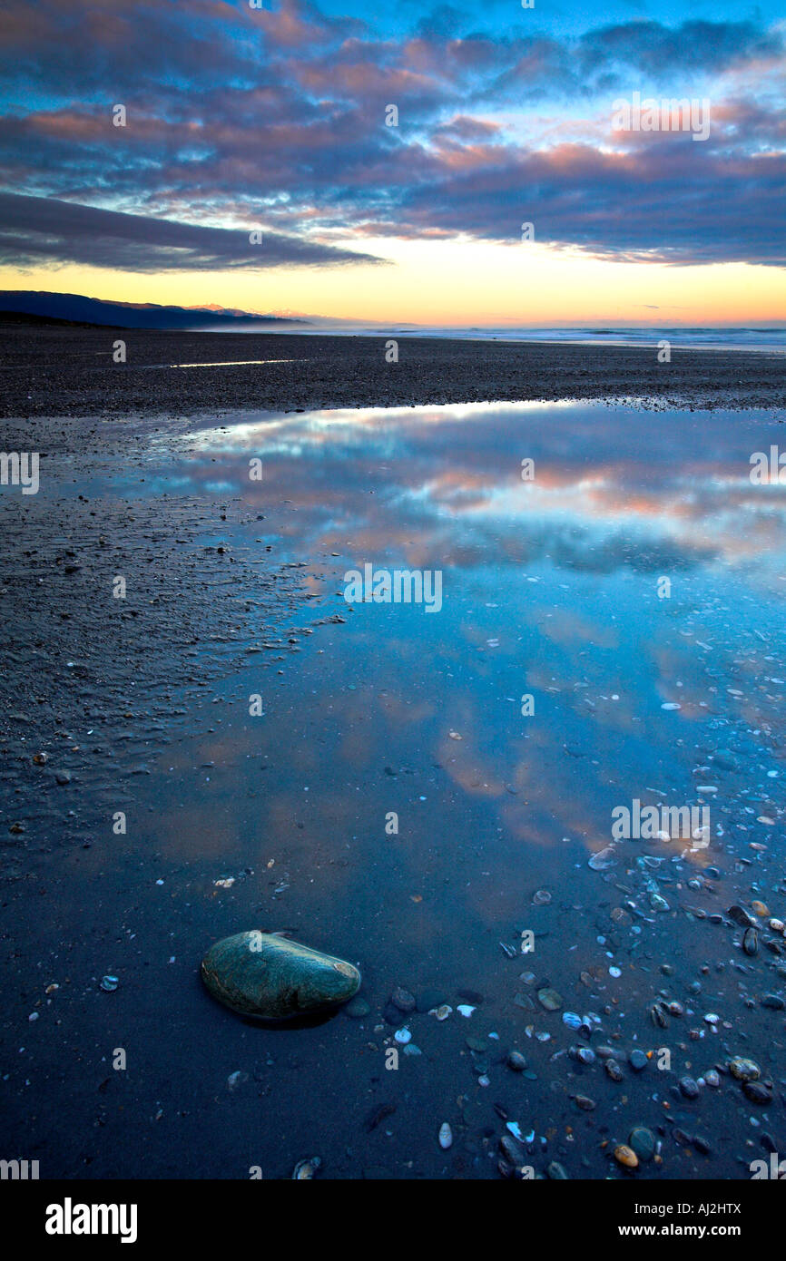A remote west coast beach at dawn the sunrise glistening on the Southern Alps mountain range in the distance, New - Stock Image