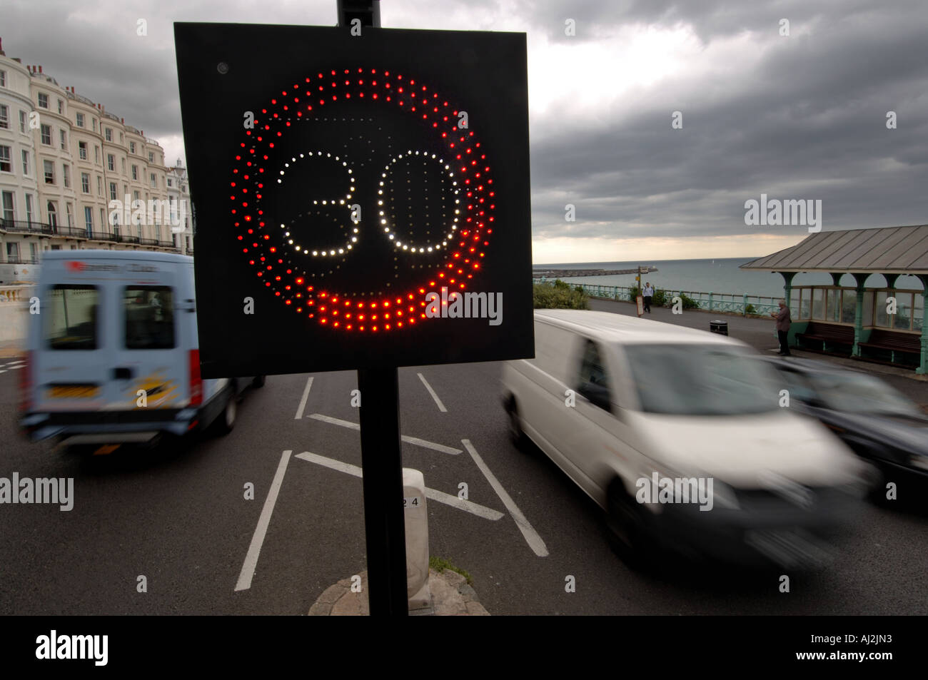 Traffic on Brighton seafront is warned of the 30 mph miles per hour speed limit by an illuminated sign - Stock Image