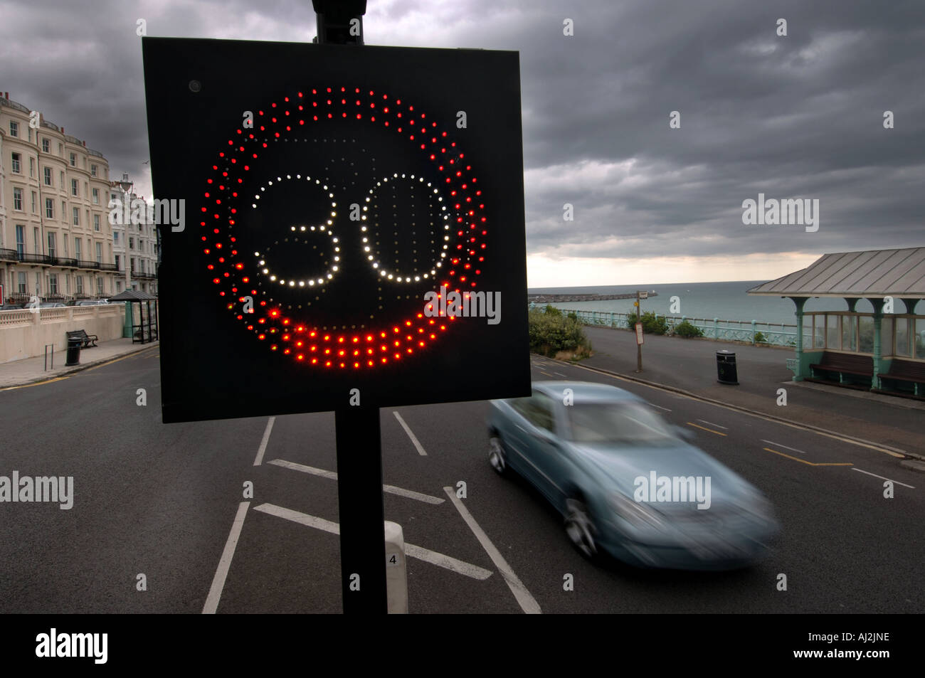 Speeding motor cars on Brighton seafront are warned of the 30 mph miles per hour speed limit by an illuminated sign - Stock Image
