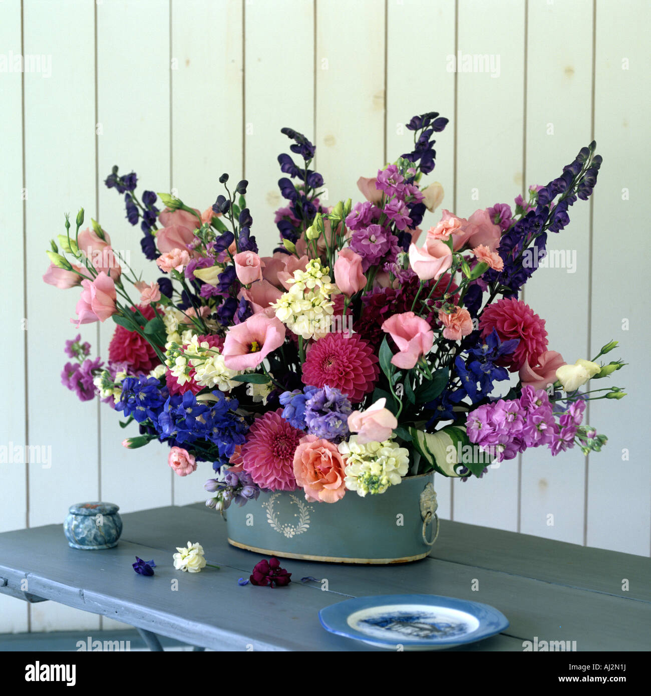 Flower arrangement  in blue pot with white cameo detail on wooden table - Stock Image