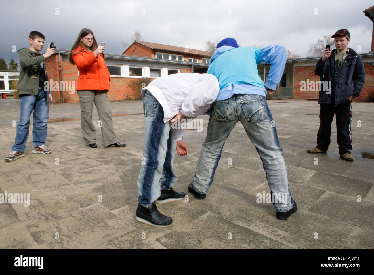 two fighting boys are being filmed by three other teenagers with their mobile phones - Stock Image