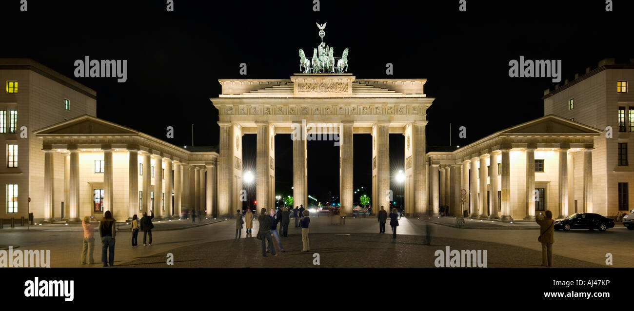 A 2 picture panoramic view of tourists taking photographs at the Brandenburger Tor or Brandenburg Gate at night. - Stock Image