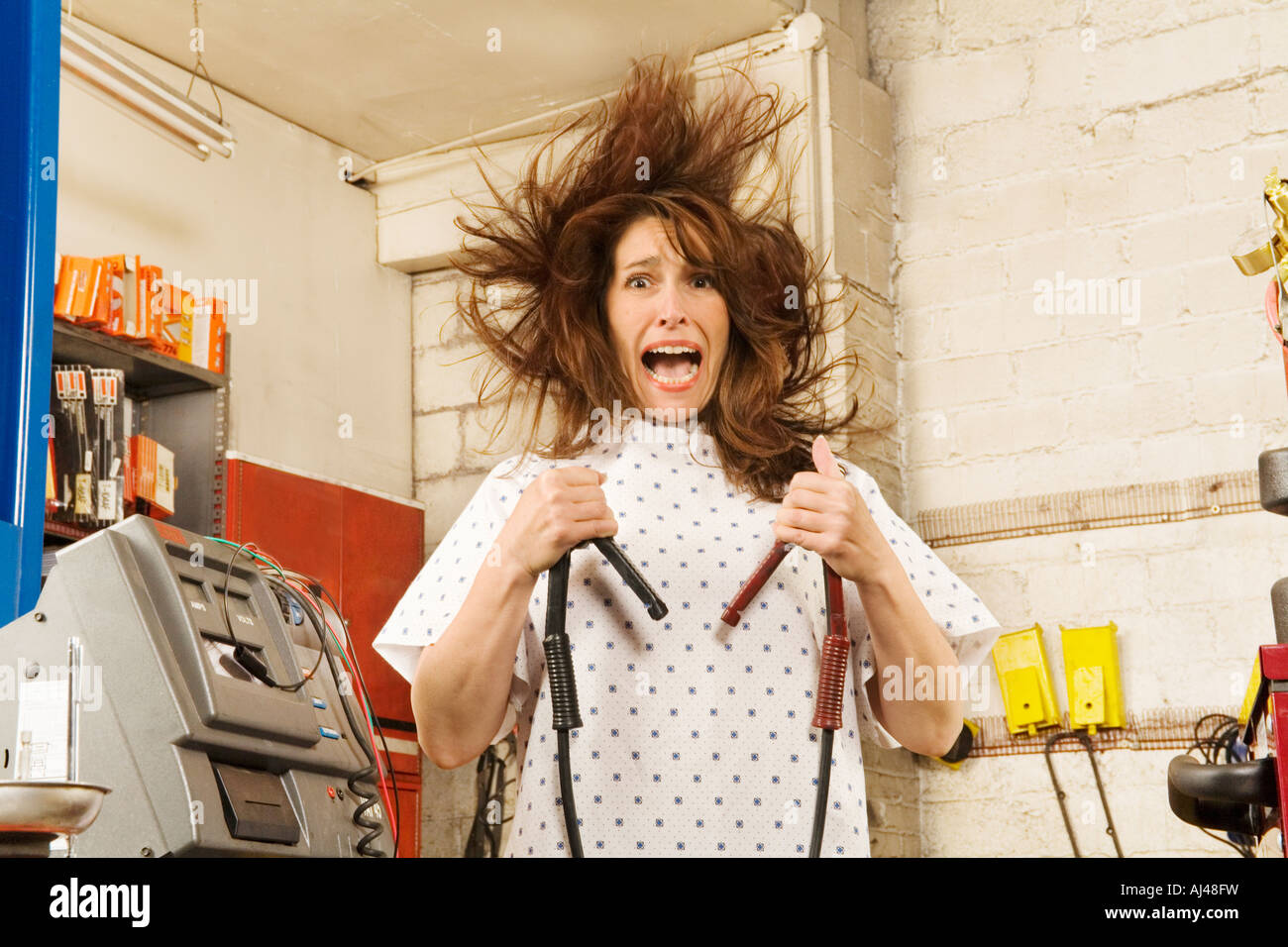 Woman in hospital gown holding jumper cables Stock Photo: 14616636 ...