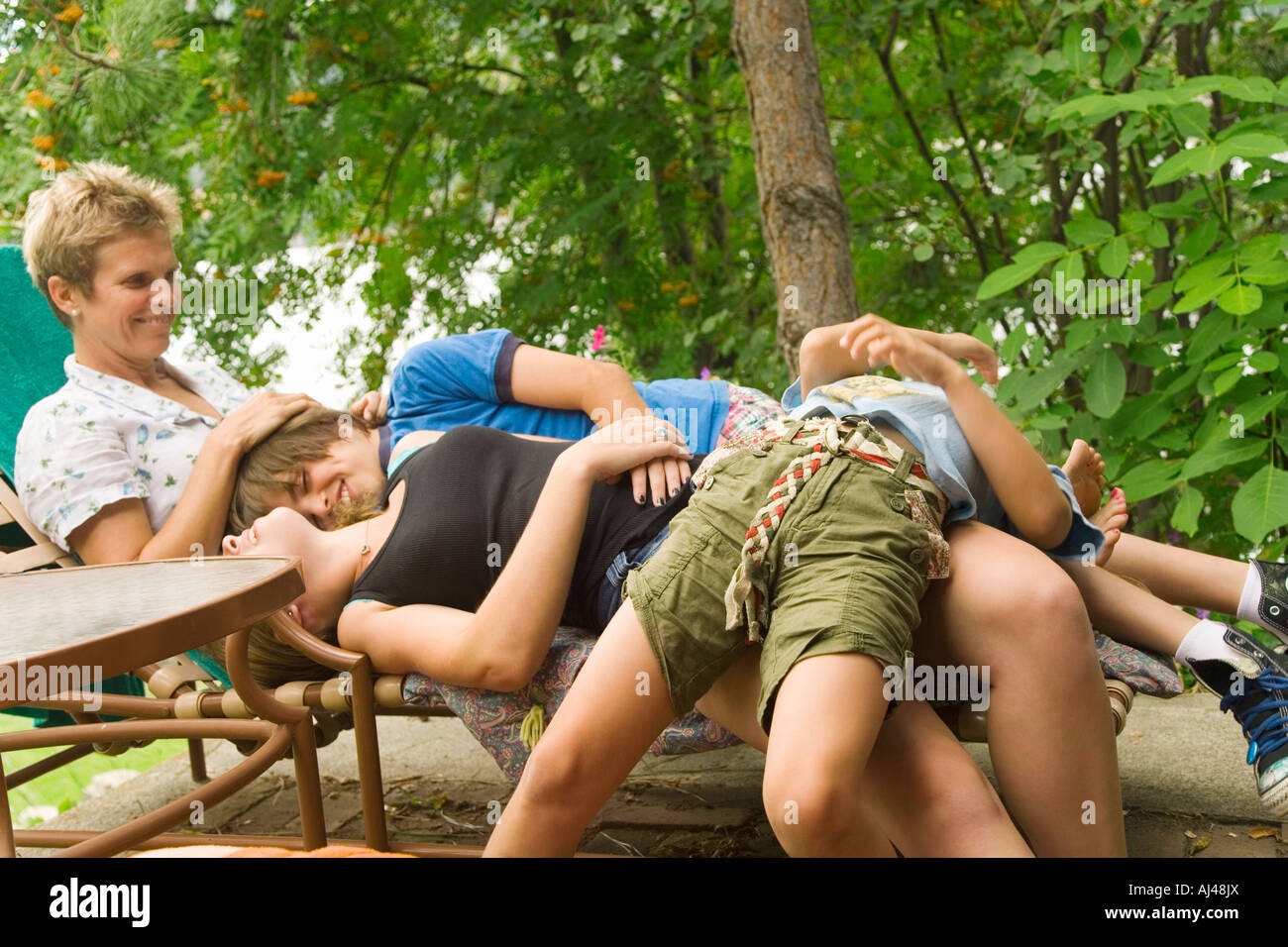 Children laying on mother in lounge chair Stock Photo