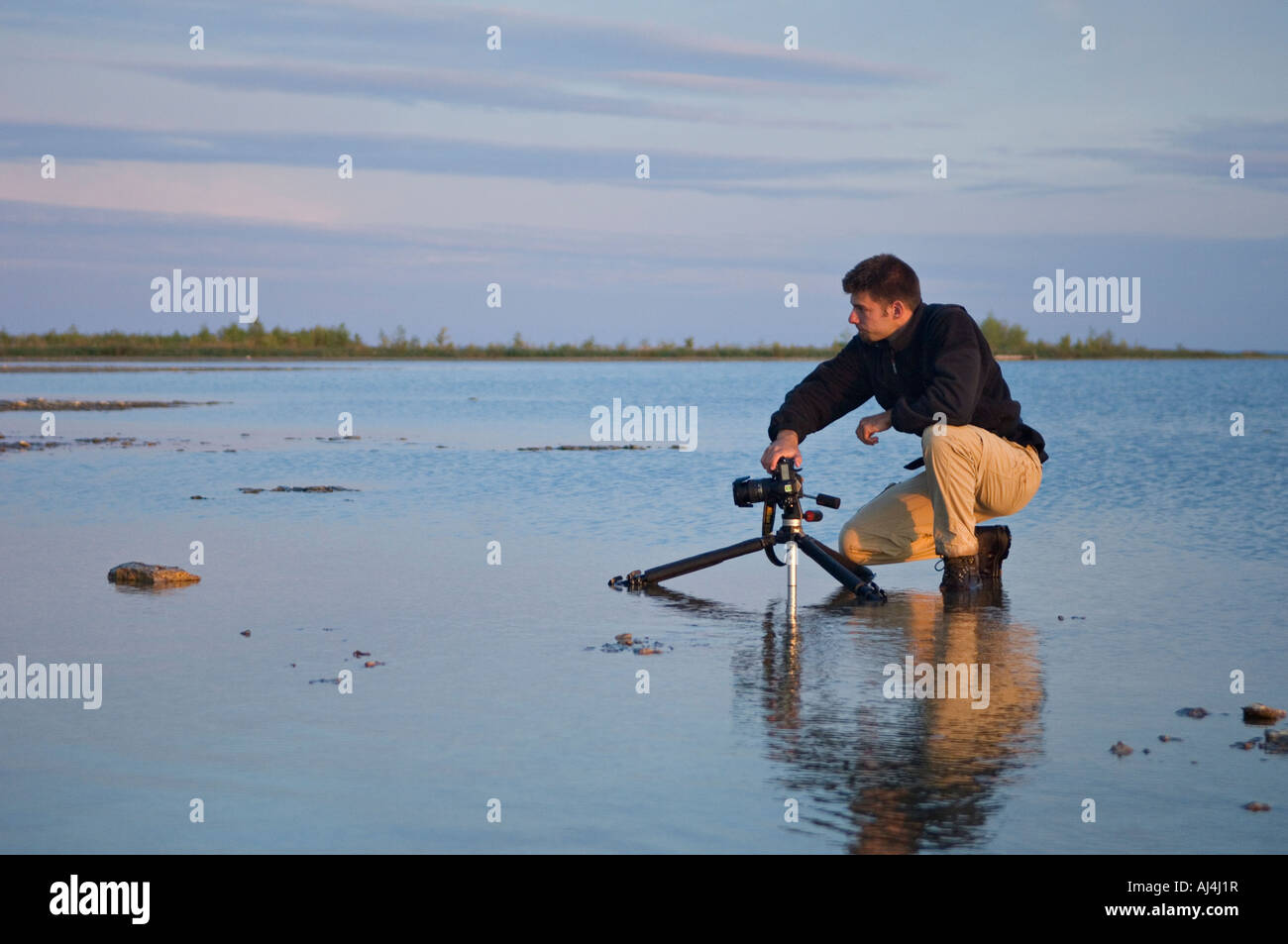 Photographer Kneeling in Shallow Water of Lake Michigan Beside Camera on Tripod Near Stonington Michigan - Stock Image