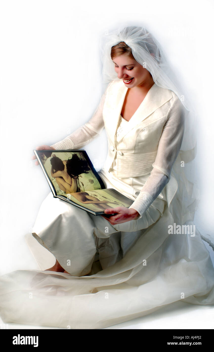 Bride lookin smiling at a sexualy tinted picture in a book. - Stock Image