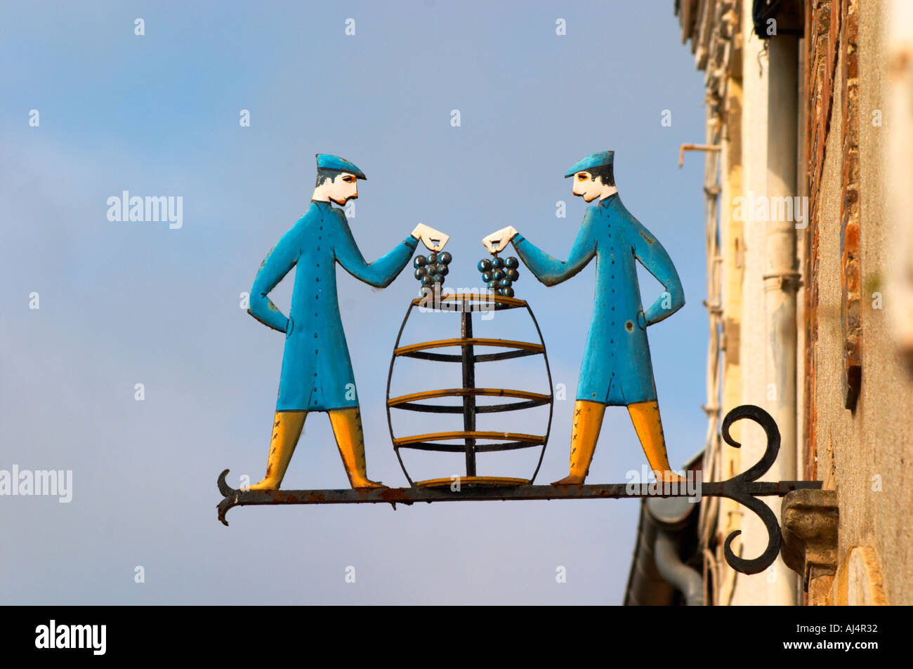 A wrought iron painted sign that illustrates the theme of champagne and wine production: two men putting grape bunches in a transparent stylised vat barrel, the village of Hautvillers in Vallee de la Marne, Champagne, Marne, Ardennes, France - Stock Image