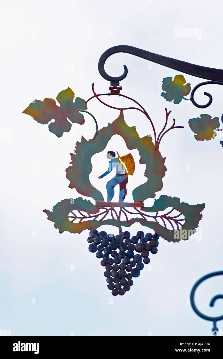 A wrought iron painted sign that illustrates the theme of champagne and wine production: a stylised vine leaf, a bunch of grapes and a man harvesting carrying a basket (hotte) on his back to collect grapes, the village of Hautvillers in Vallee de la Marne, Champagne, Marne, Ardennes, France - Stock Image