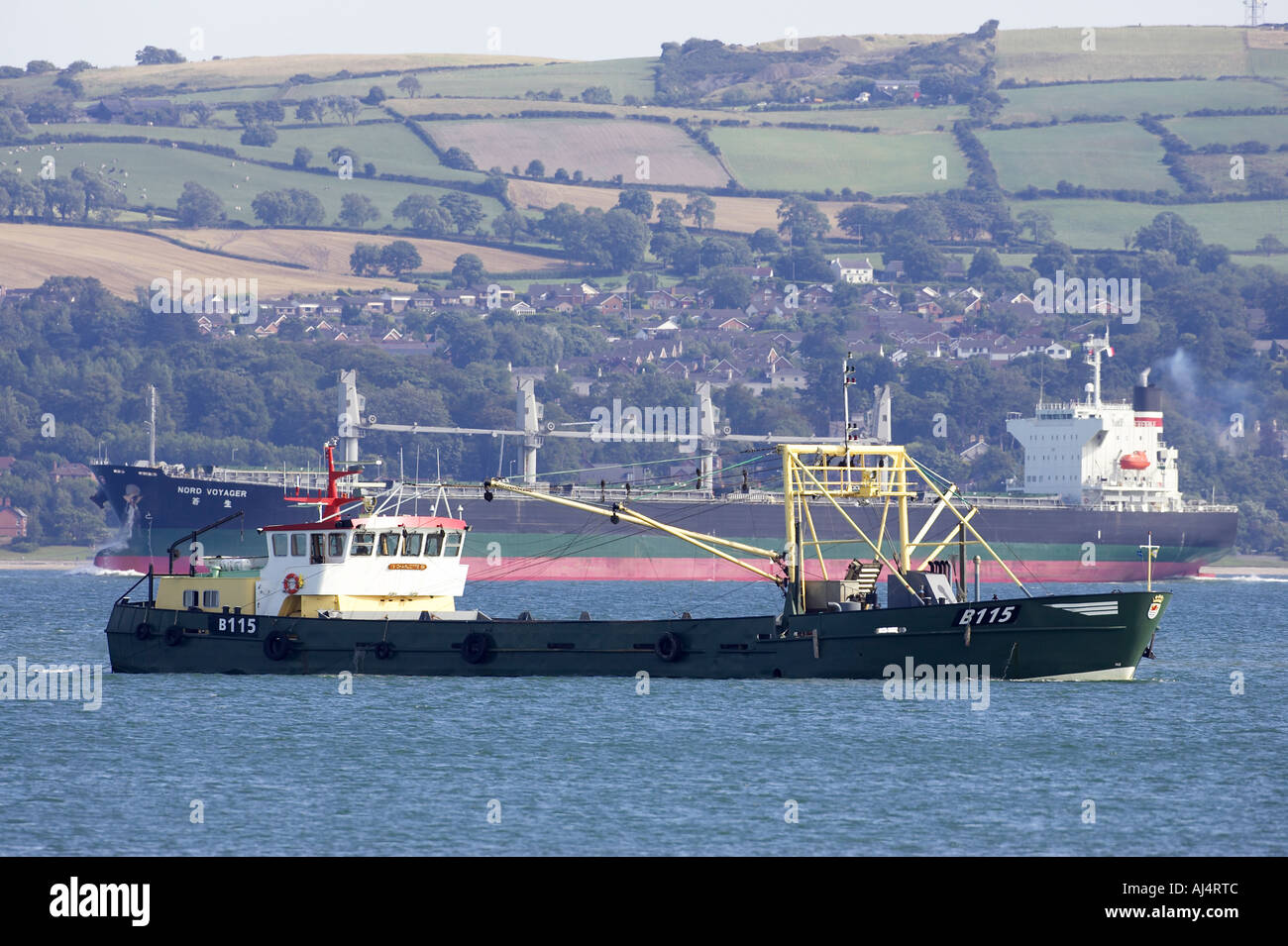 nord voyager bulk carrier ship passes large mussel fishing boat trawling dregding for mussels at sea off holywood - Stock Image