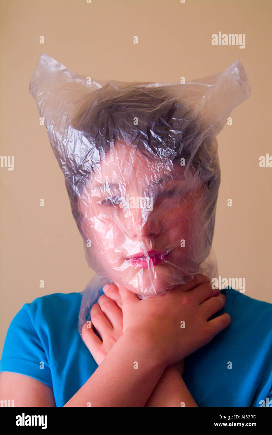Young girl with head in a plastic bag - Stock Image