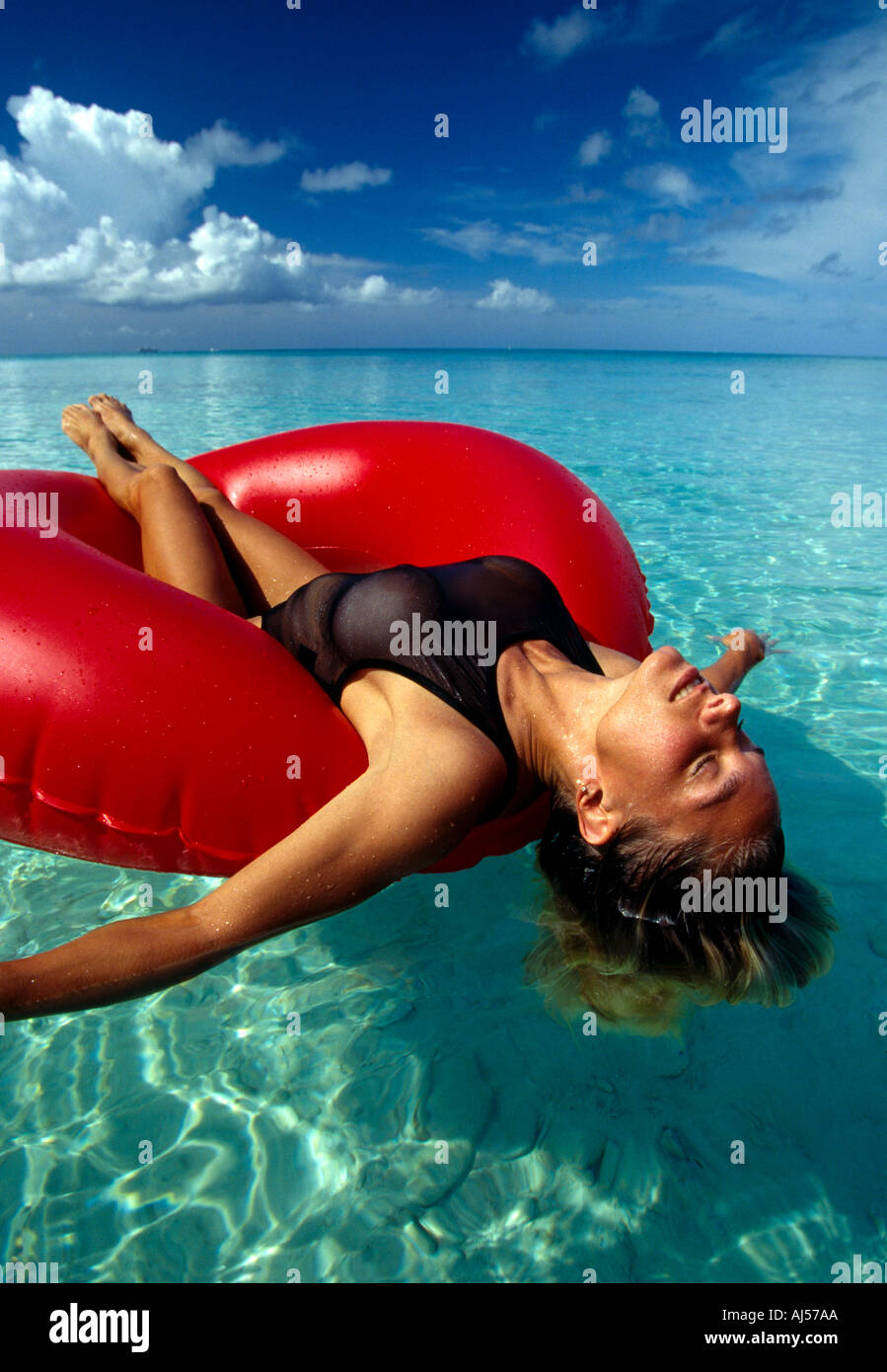 Cayman Islands Grand Cayman 7 Mile Beach woman on red float in water - Stock Image