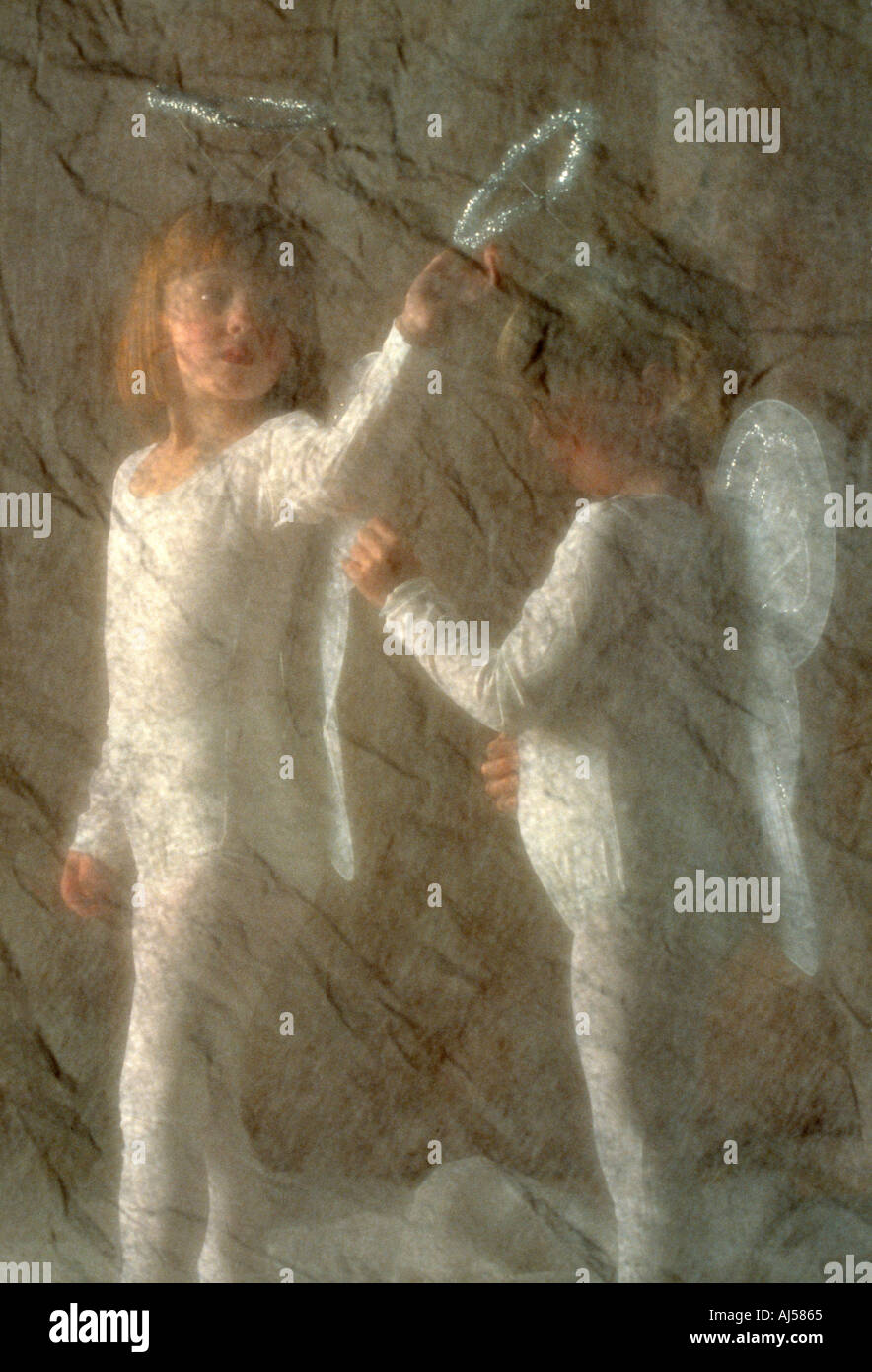 Little Caucasian gils dressing up in angel costumes for performing in dance recital - Stock Image