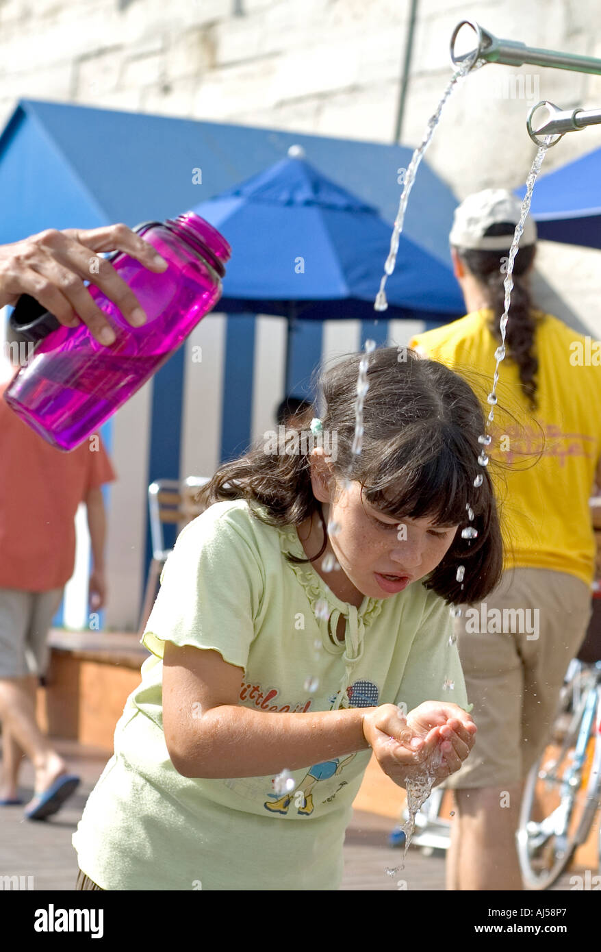 Thirsty people drinking from a  public fountain set up for Paris Plage, during the summer heatwave, Paris, France. - Stock Image