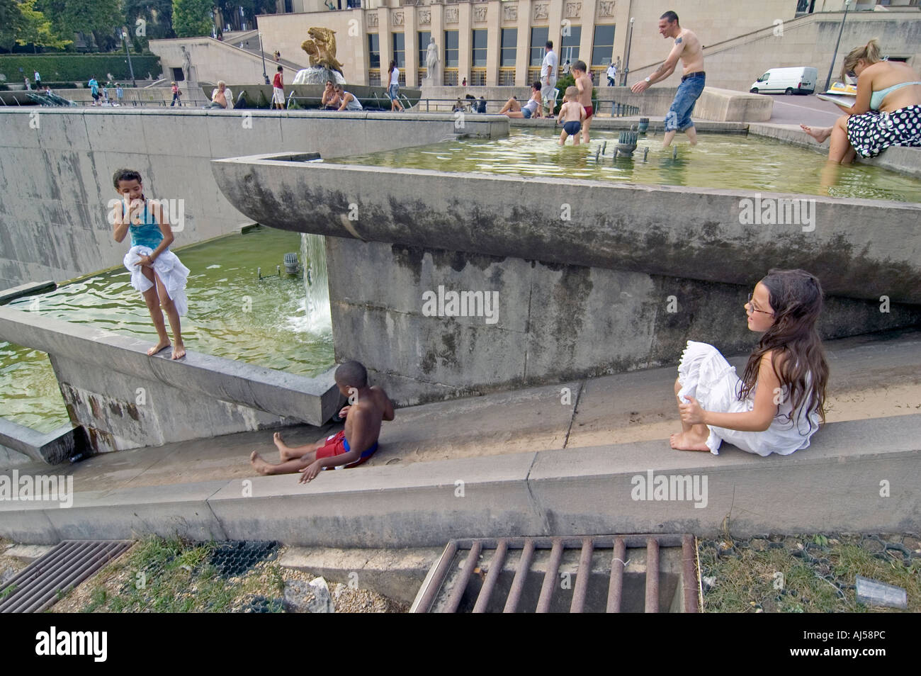 Kids playing in the fountain and pond of the Champ de Mars esplanade during the heatwave, Paris, France. - Stock Image