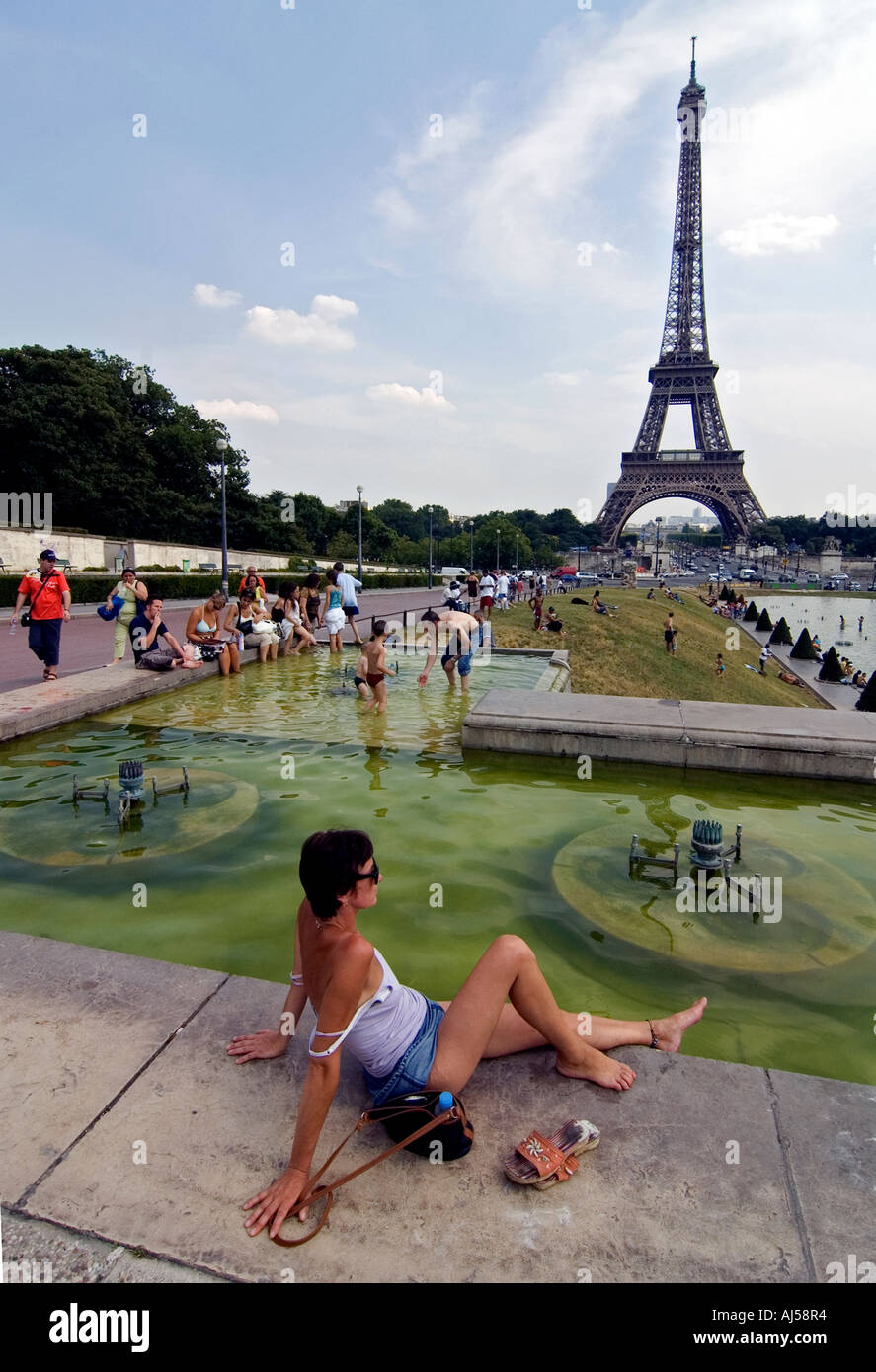 Woman relaxing near fountain and pond of the Champ de Mars esplanade during the heatwave, Paris, France. - Stock Image