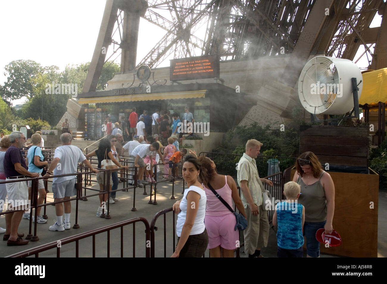 Tourists waiting to visit the Eiffel tower under sprayed mist, during the summer heatwave, Paris, France - Stock Image