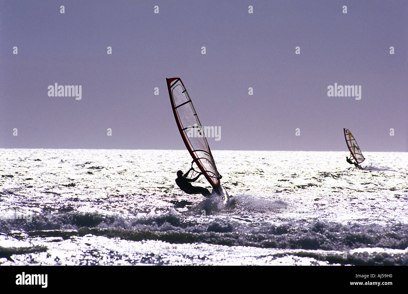 Two windsurfers head out to sea - Stock Image