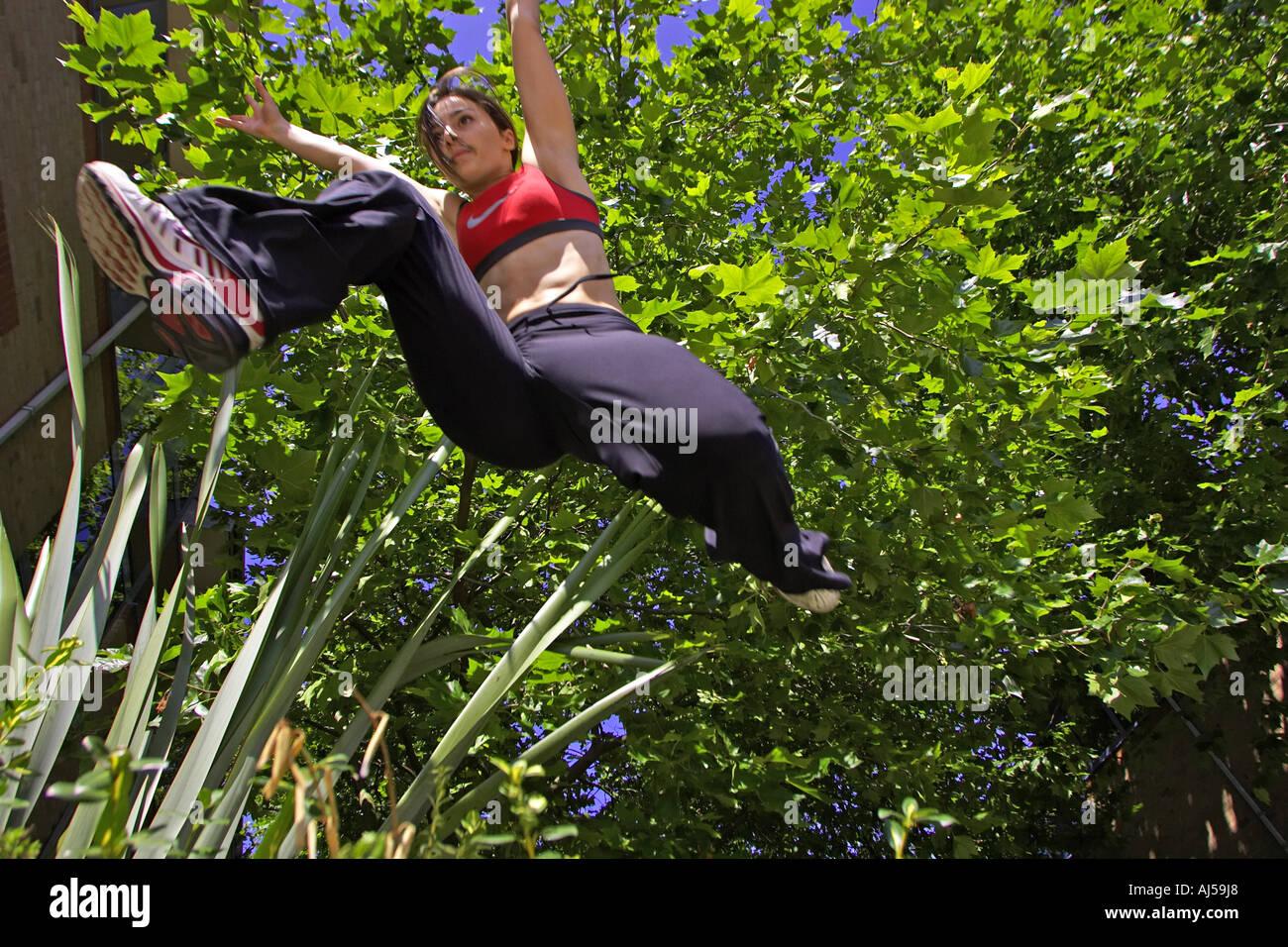 Women performs le Parkour leap - Stock Image