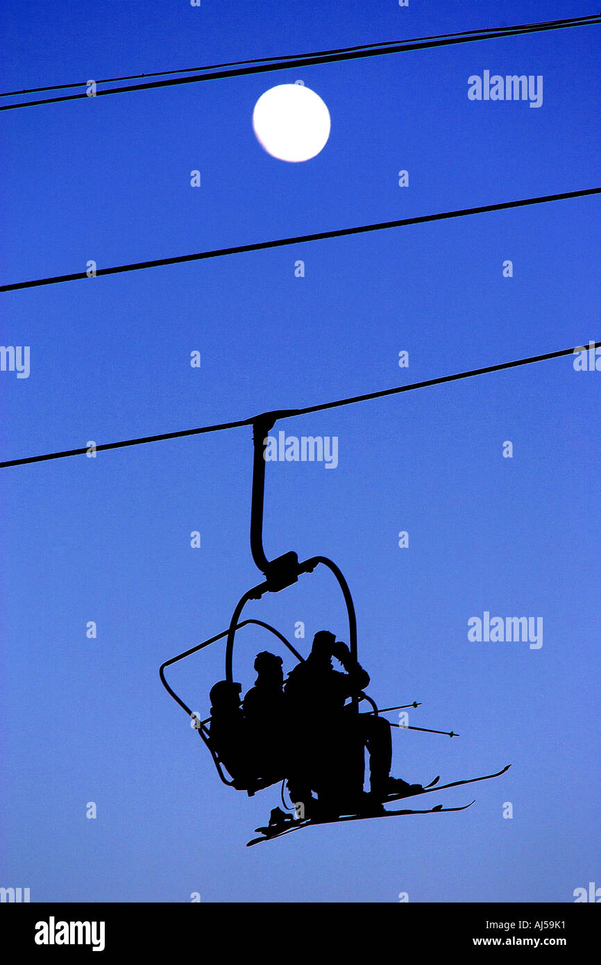 three skiers ride the last lift - Stock Image