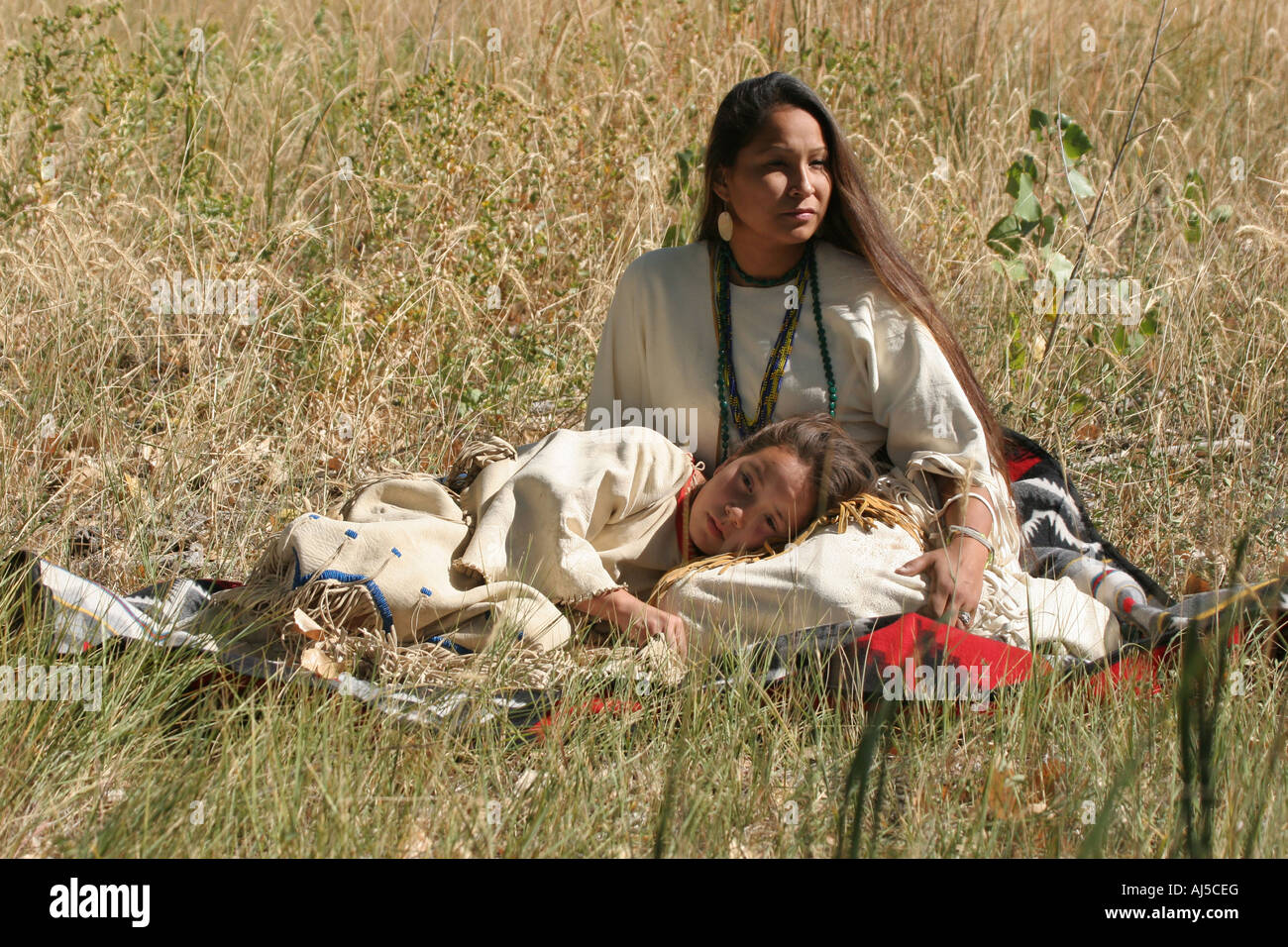 Native American Sioux Indian Women and child sitting on a blanket in the long grass - Stock Image