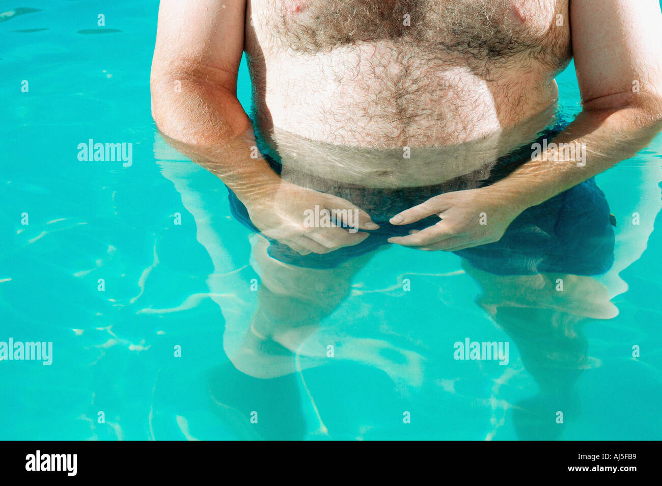 Overweight man in swimming pool - Stock Image