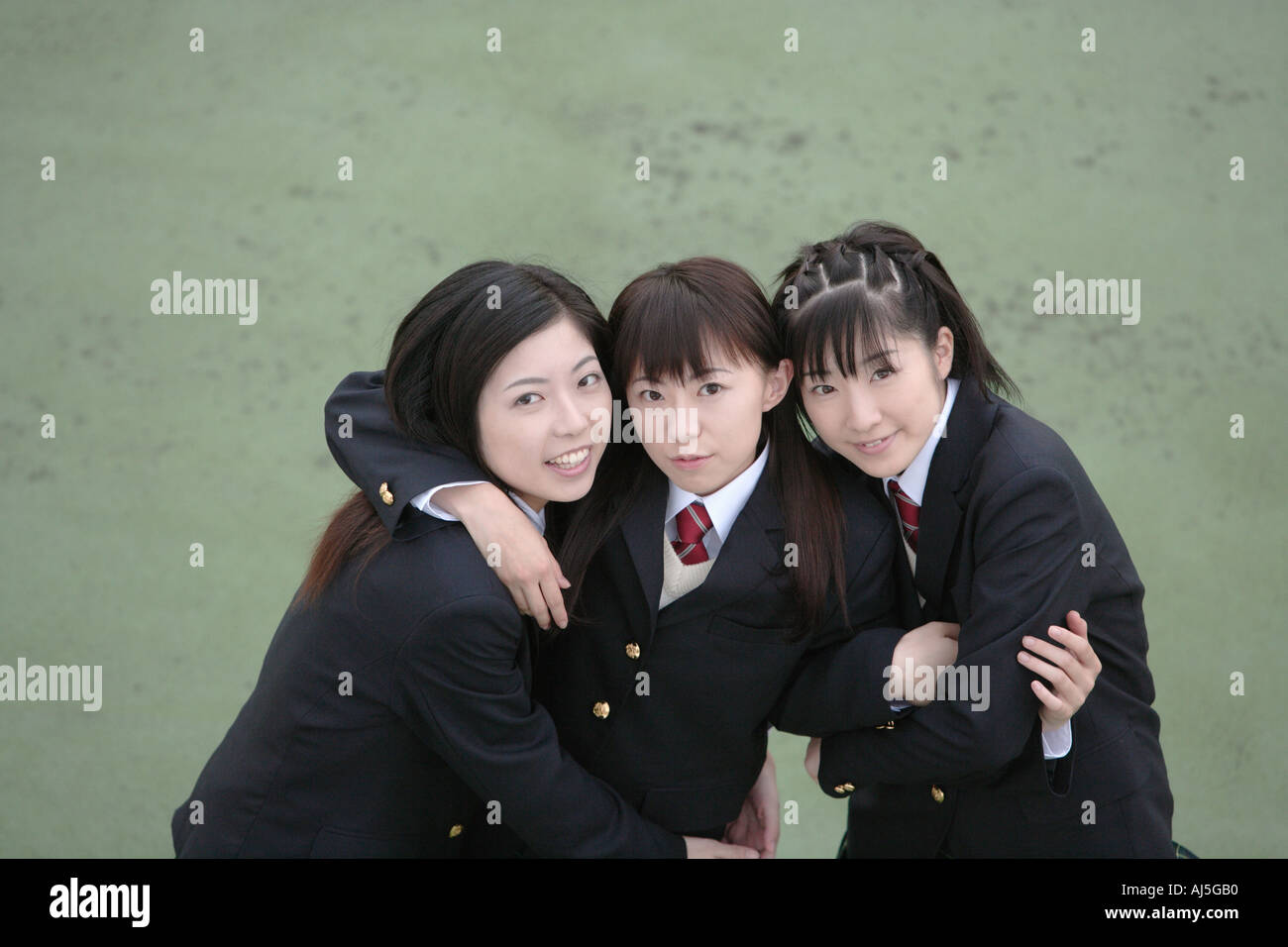 Three high school girls with arms around each other smiling Stock Photo