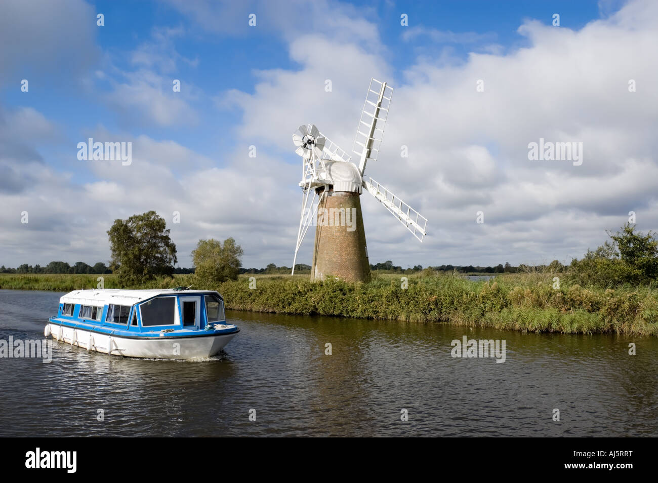 Blue boat passes Turf Fen Windpump on the River Ant, How Hill, Norfolk Broads, East Anglia, England, UKStock Photo