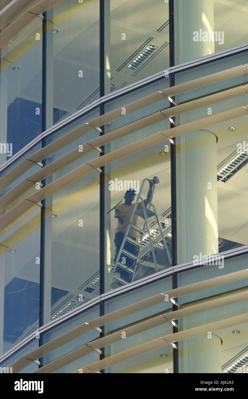 Window cleaner at work in new empty office block - Stock Image