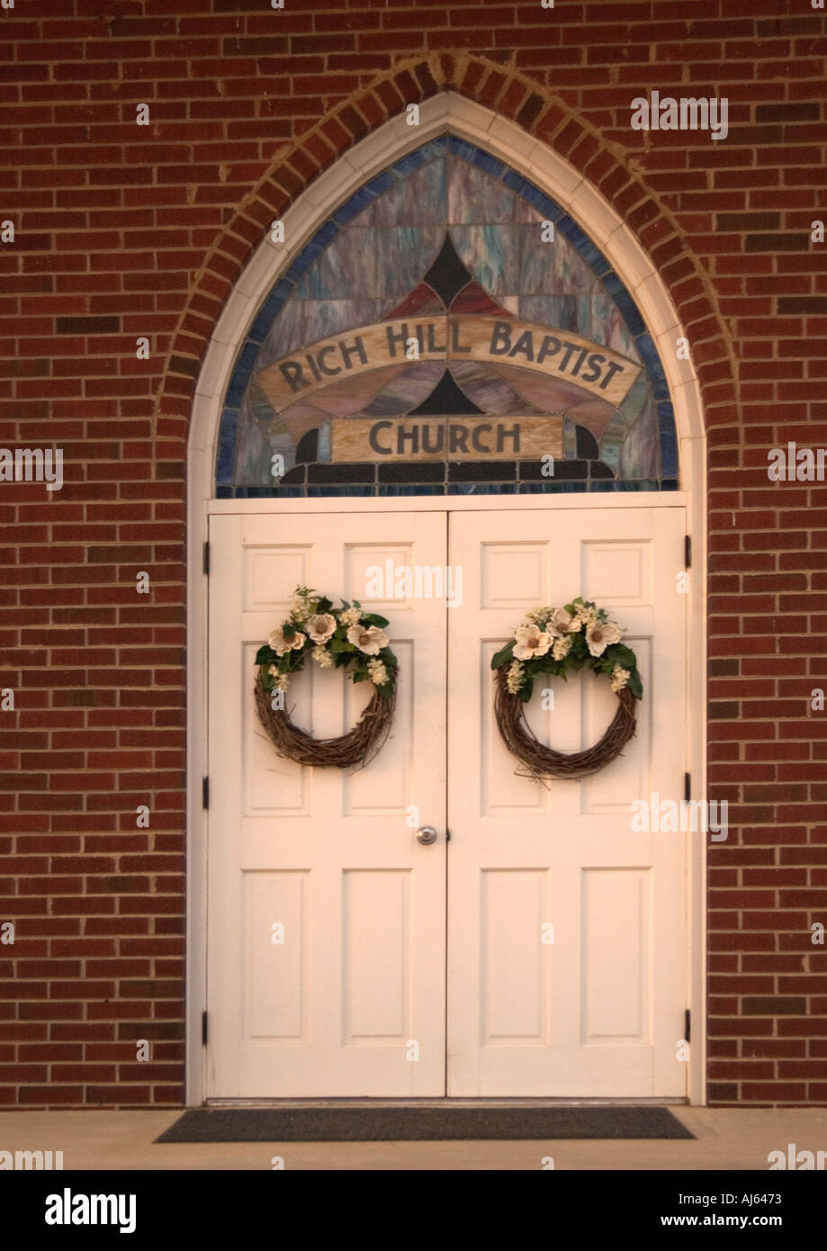 Wreaths Hanging On White Church Door With Stained Glass Window USA