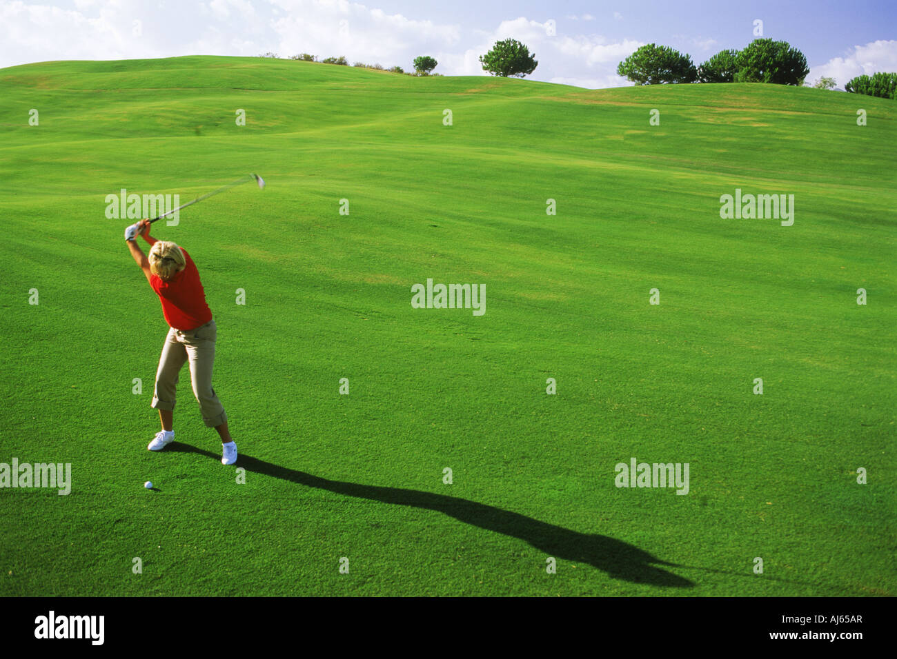 Woman hitting with iron off lush green fairway - Stock Image