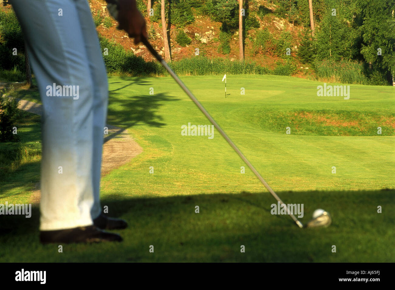 Golfer hitting with iron off lush green fairway - Stock Image