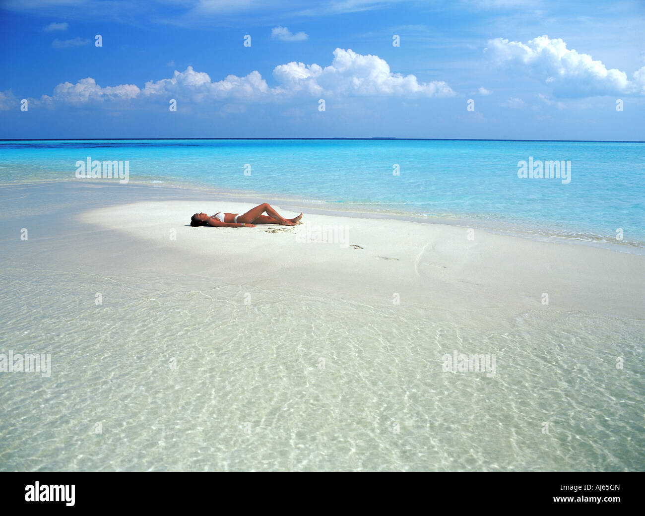 Woman alone on sandbar in Maldive Islands surrounded by Indian Ocean - Stock Image