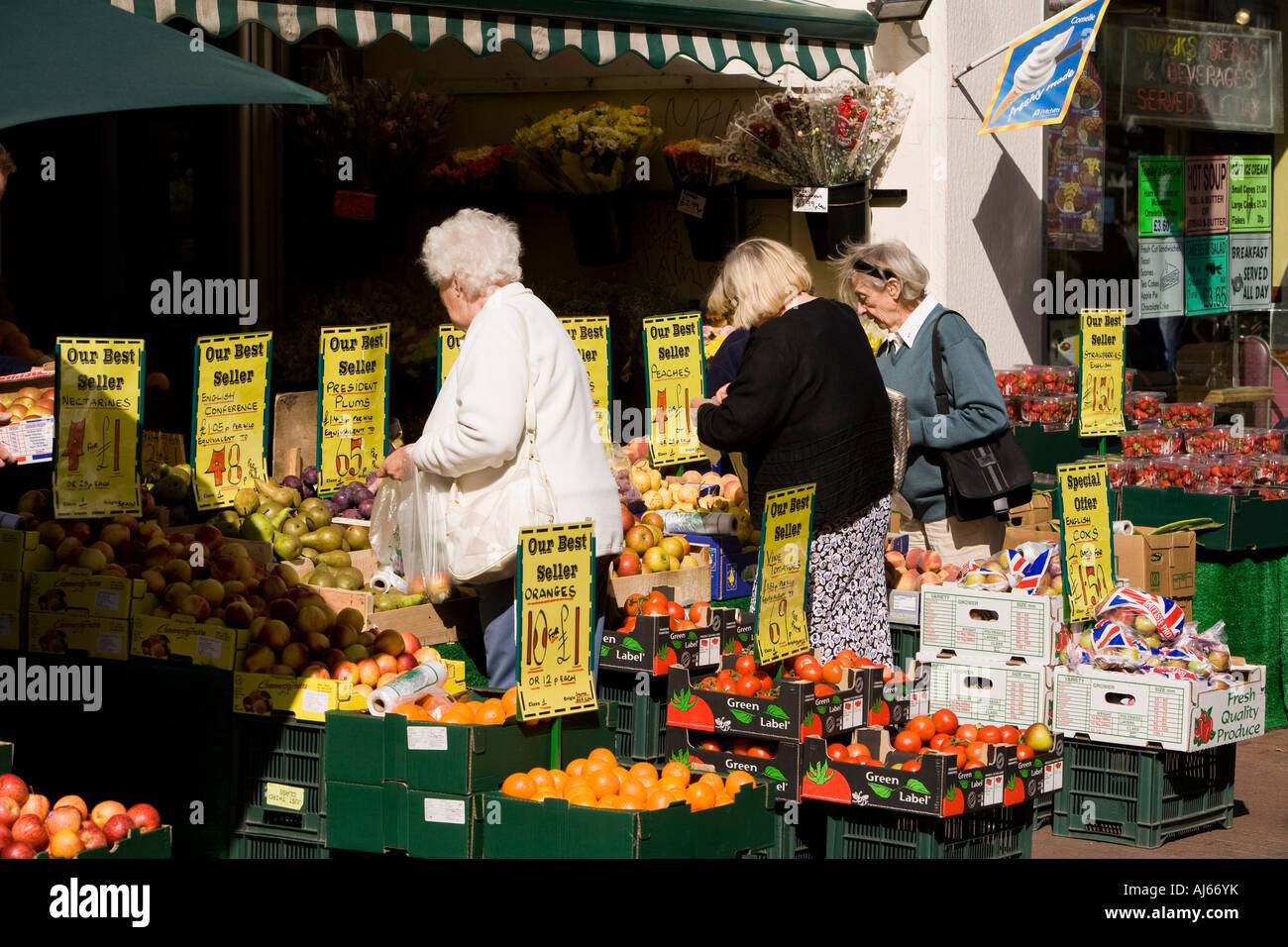 UK Kent Deal High Street shoppers viewing fresh fruit for sale in greengrocers - Stock Image