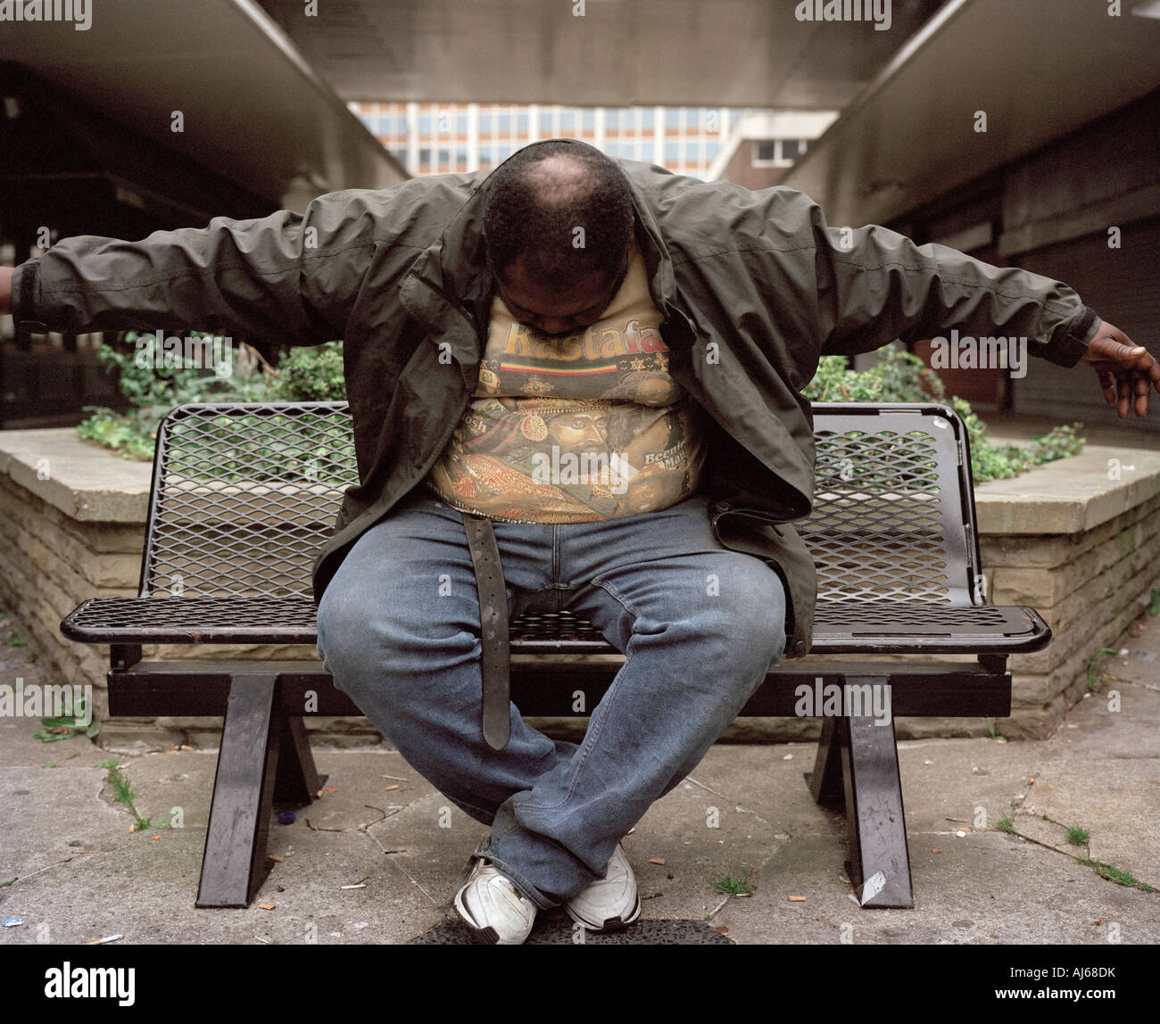 A west Indian man on a bench showing abnormal social behavior, London, England, UK. - Stock Image