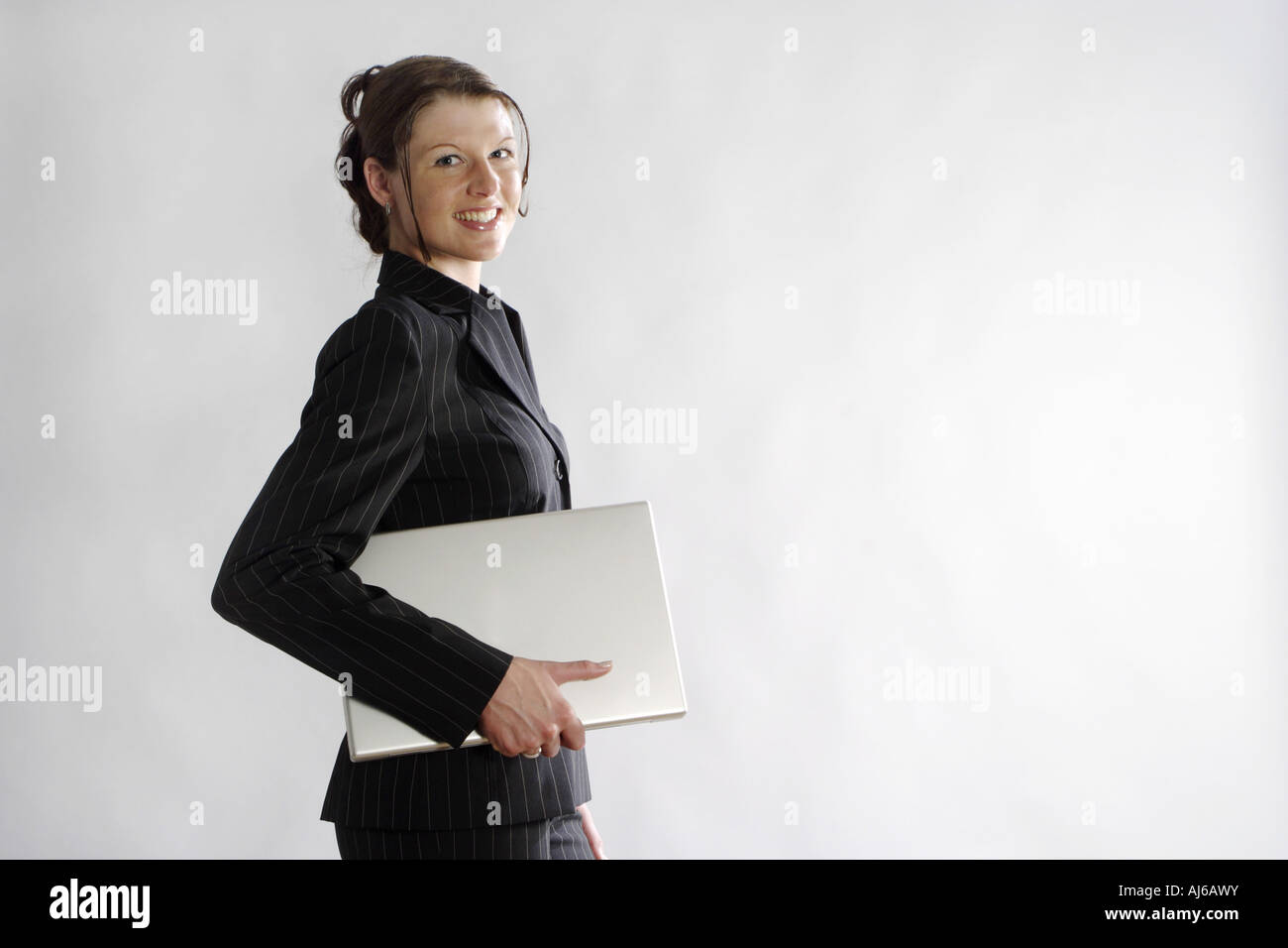 young woman in bussiness outfit with laptop under her arm, Germany Stock Photo