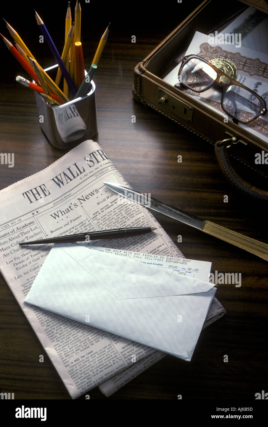 Desktop still life with pencils envelope pen letter opener Wall Street Journal and brief case - Stock Image