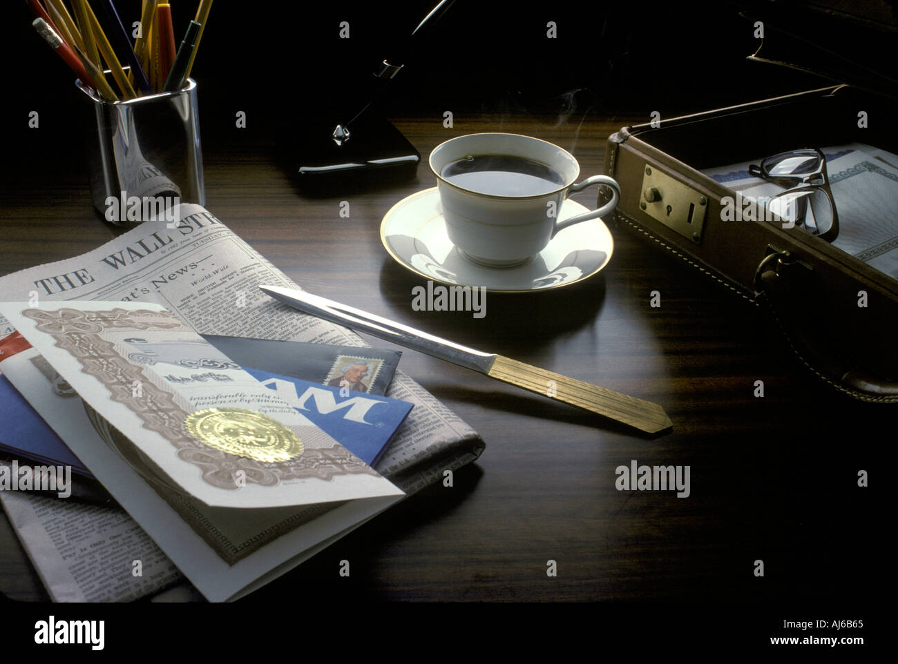 Desktop still life with stock certificate coffee cup letter opener Wall Street Journal and brief case - Stock Image