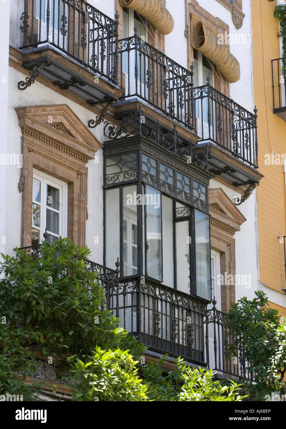 Open and enclosed balconies on a residential street in Seville Spain - Stock Image