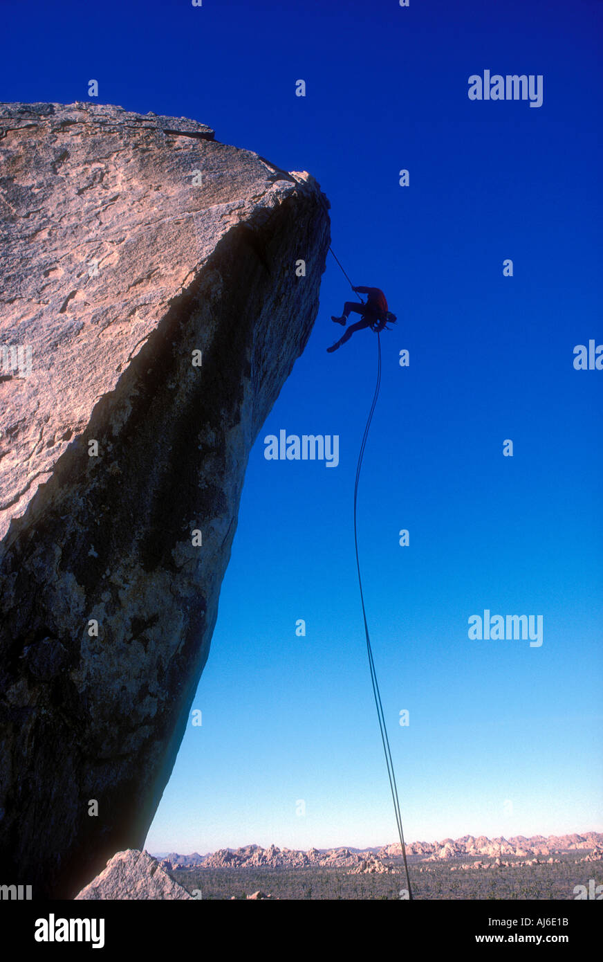Rock climber rappeling off of large boulder in Joshua Tree National Monument California Model Released Image - Stock Image