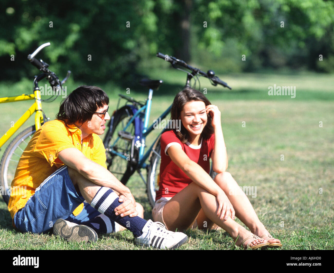 Young couple using their mobile phones while having a rest after a bike ride. - Stock Image
