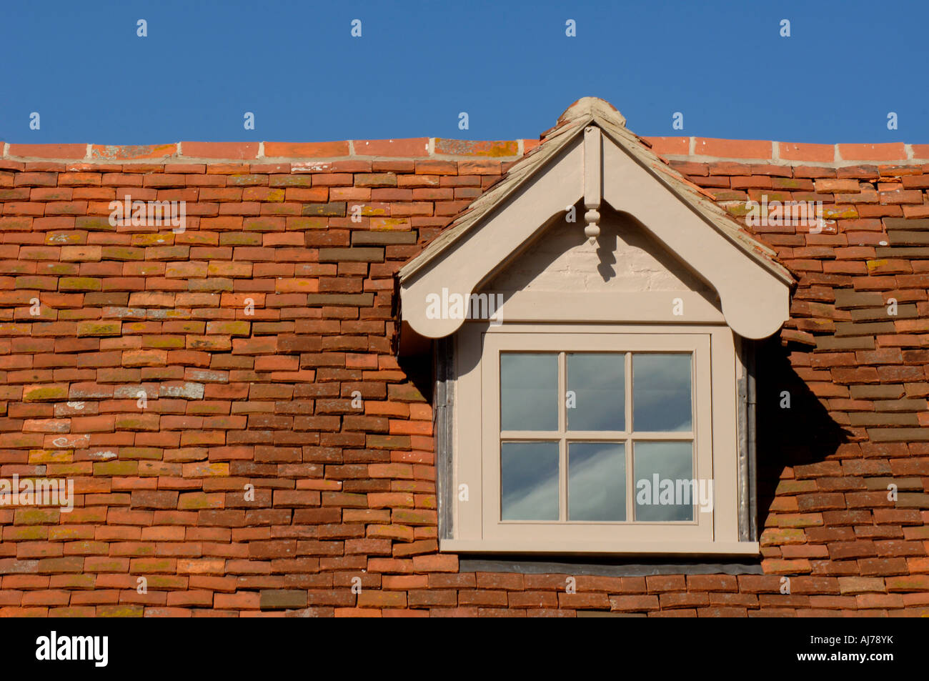 Traditional style tiled roof with dormer window set against a blue sky. Sidlesham, near Selsey. Photograph by Jim Stock Photo