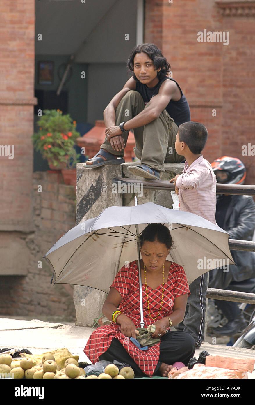 Nepali woman counting her money at market Young man looks on Kathmandhu Nepal - Stock Image