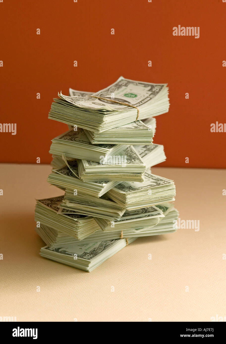 stack of money in pile with dollars on orange background - Stock Image