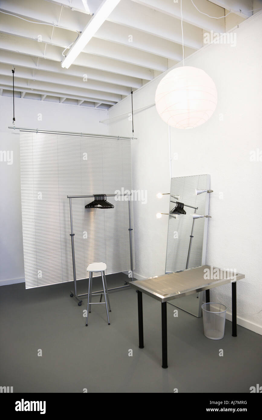 Workspace with table chair mirror clothing rack and room divider - Stock Image
