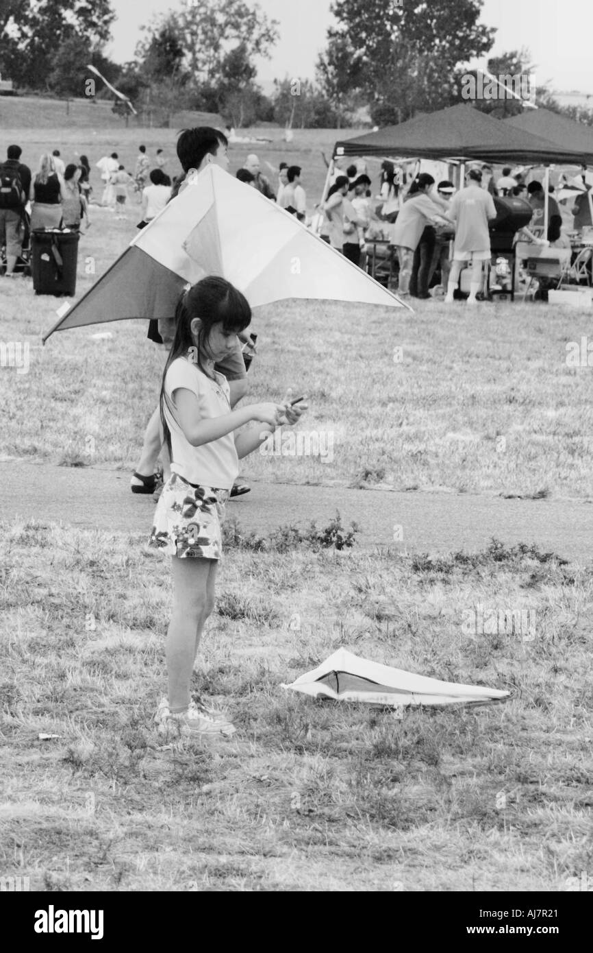 Young asian girl flying a kite in black and white - Stock Image