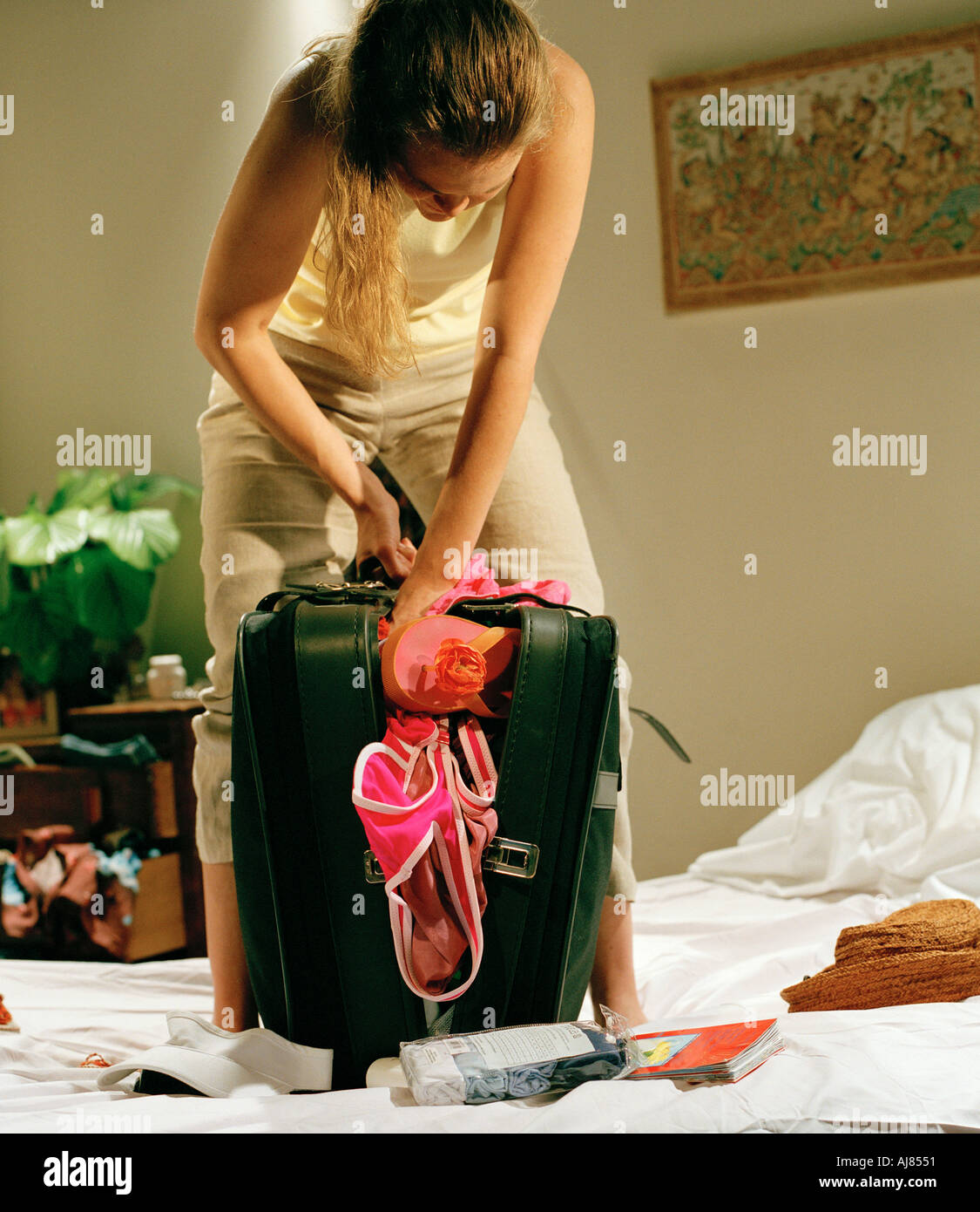 woman standing on bed closing over packed suitcase - Stock Image
