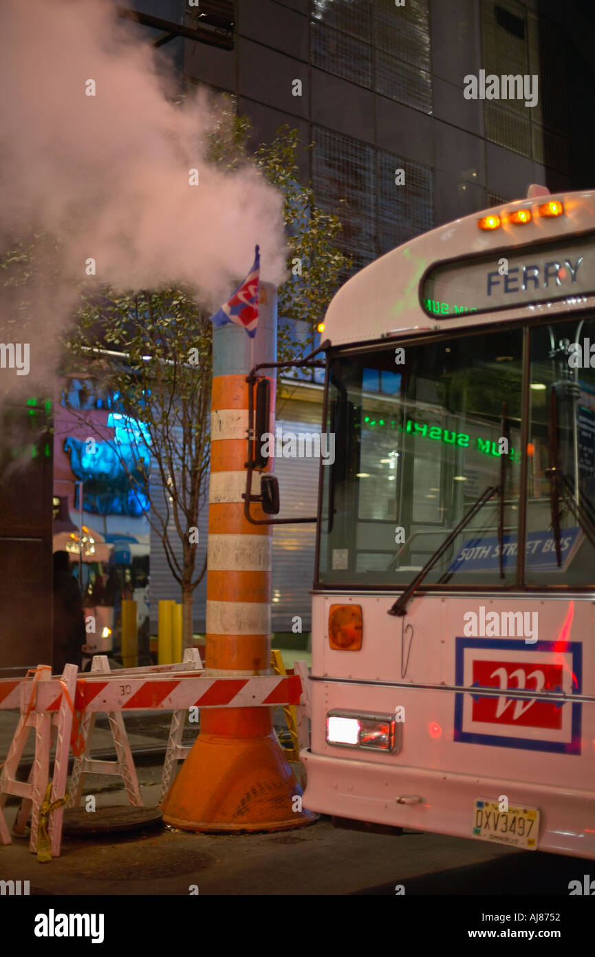 MTA Ferry bus passes orange steam vent in street in Times Square at West 49th Street and Broadway New York NY - Stock Image
