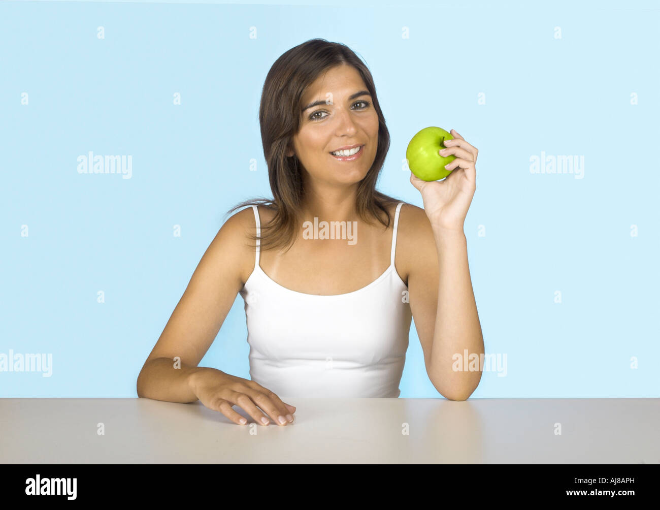 Beautiful young woman holding a green apple - Stock Image